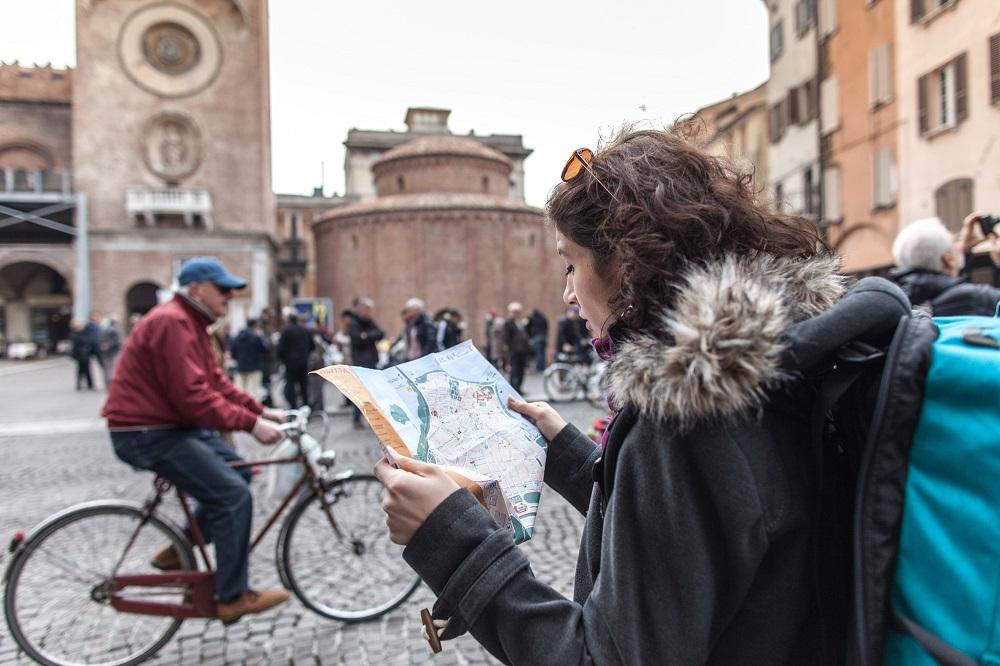Piazza Erbe ragazza con cartina - Foto Archivio Comune di Mantova_ridotta